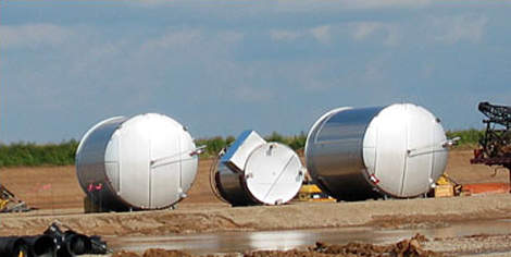 Stainless steel milk storage silos delivered to the site prior to installation.