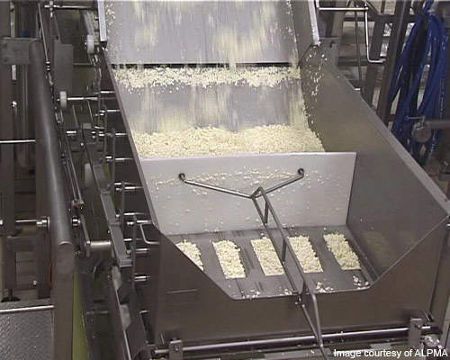 A filler unit used to fill food-grade plastic with cheese curd.