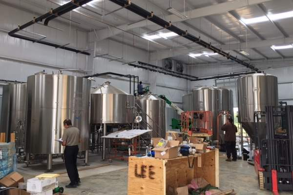 Four 60bbl fermenters, a 120bbl fermenter, a 60bbl and 120bbl brite tank, and a 7bbl coolship were delivered by Craftwerk Brewing Systems in September 2015. Image courtesy of Omaha Brewing Company.