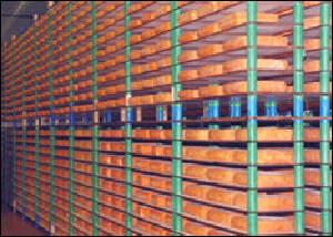 Gouda cheeses maturing in environmentally controlled racks.