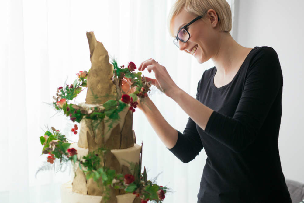 A woman decorates a gluten-free cake with flowers.