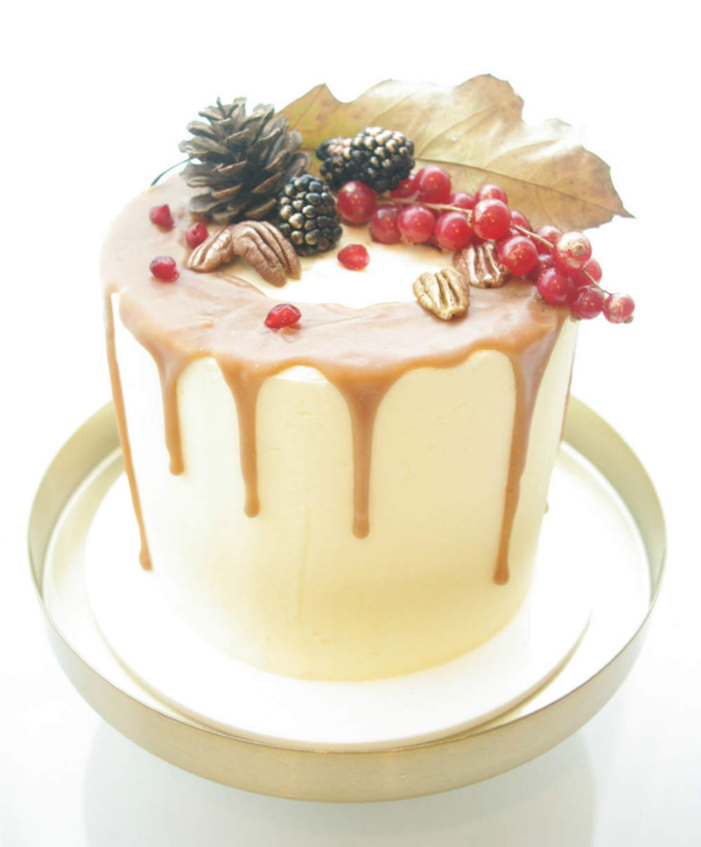 A gluten-free nut drizzle cake, decorated with berries, nuts and pine cones.