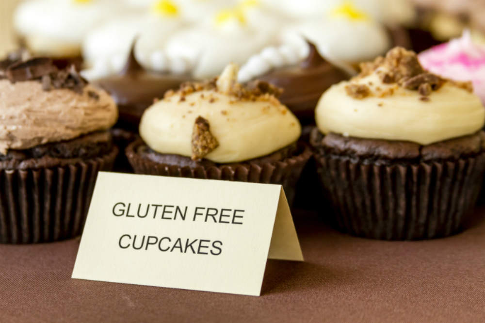 Gluten-free decorated cupcakes displayed in front of a label